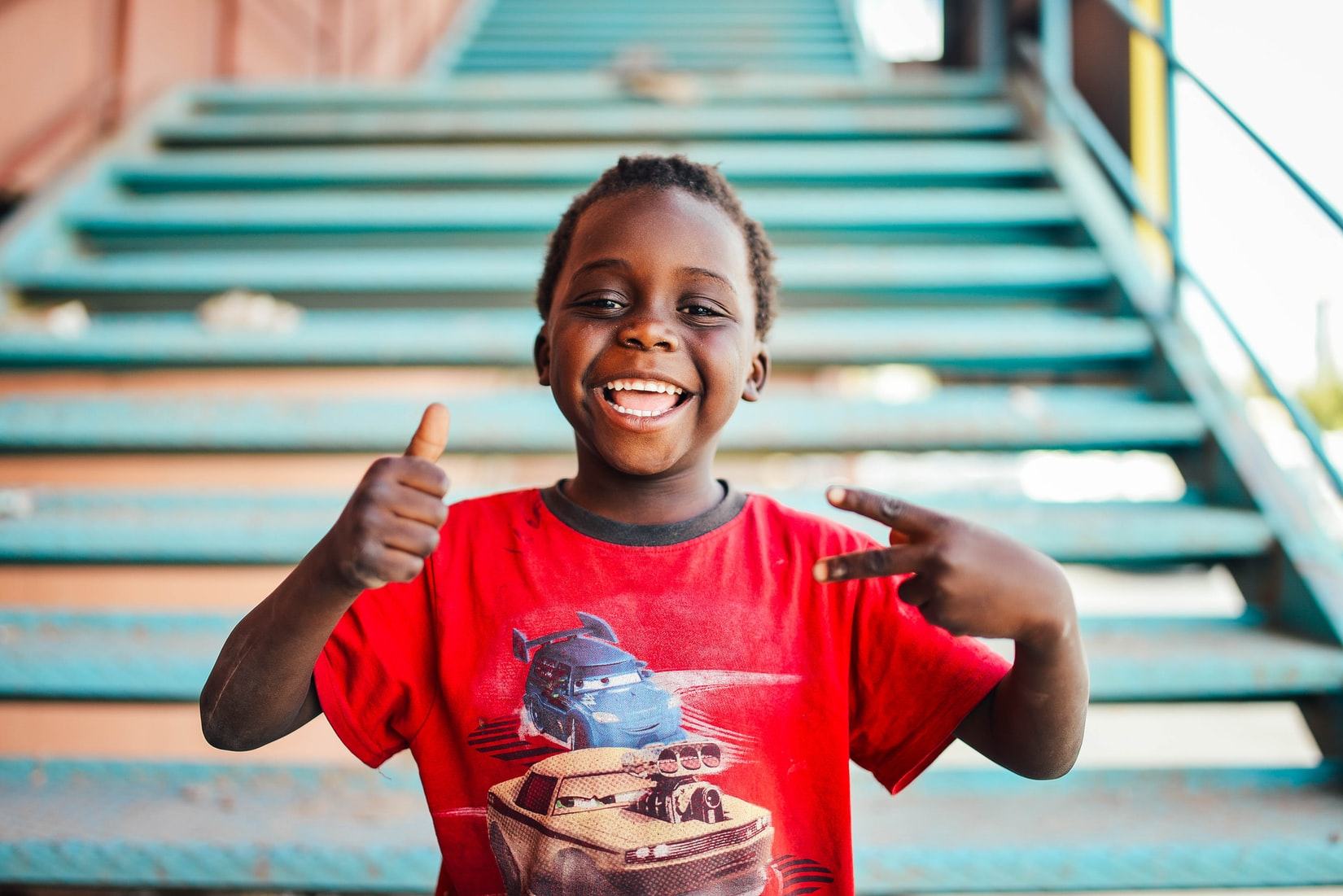 A young boy, wearing a red Cars T shirt and a big smile, stands in front of a turquoise outdoor staircase. He gives a thumbs up with one hand and a peace sign with the other