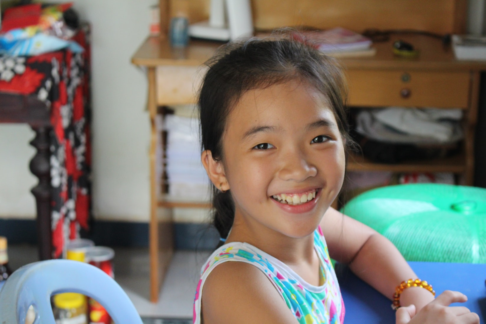 A young girl smiles toward the camera - she is in a multicolored tank top and seated comfortably in a common area